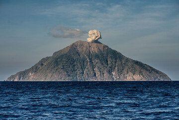 Batu Tara volcano (Komba Island) with an eruption seen from a distance at sea. (Photo: Tom Pfeiffer)