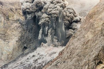 Moderately strong explosion with large bombs and blocks ejected, leaving ash trails in the air. (Photo: Tom Pfeiffer)
