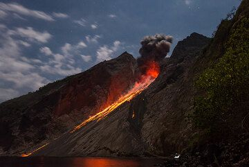 Normal-sized strombolian eruption in the moonlight. Observer's headlamp in the lower right. (Photo: Tom Pfeiffer)
