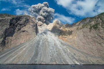 Some local fishermen seem unimpressed by the eruption, which puts their boats in danger by projectiles and (as observed during previous occasions) pyroclastic flows. (Photo: Tom Pfeiffer)