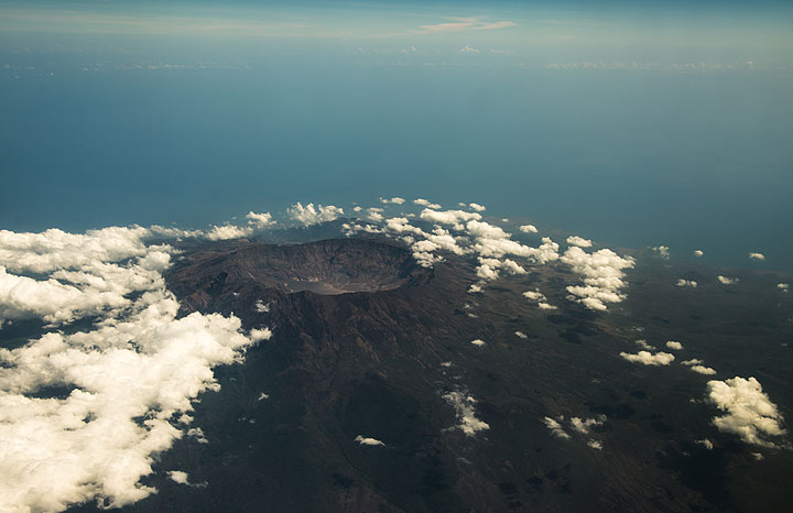 The large circular summit caldera of Tambora volcano (Sumbawa Island, Indonesia) which exploded in 1815 during the world's largest known explosive volcanic eruption in history on record. (Photo: Tom Pfeiffer)