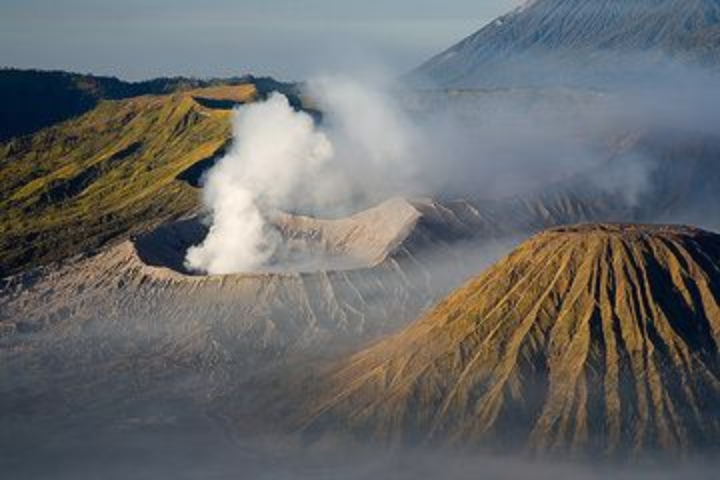 Smoking Bromo volcano and Batok cone with its deep radial erosion gullies (Photo: Tom Pfeiffer)