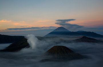 Sunrays illuminate high clouds, while the caldera is still in the shadow. (c)