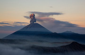 Erste Sonnenstrahlen erreichen die Aschenwolke, die der Semeru Vulkan soeben ausgestoßen hat. (c)