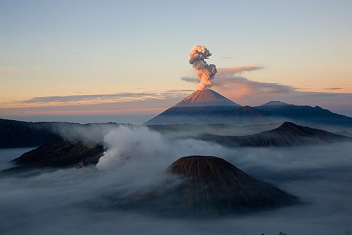 Niebla en la caldera, fumando una erupción del volcán Semeru sol temprano, Bromo y el cono de cenizas de Batok (c)