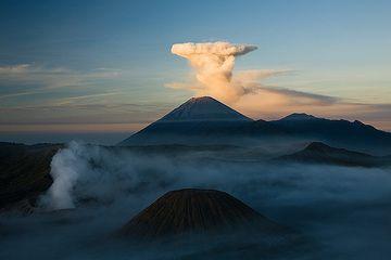 Umbrella cloud over Semeru, smoking Bromo volcano in the misty shadow (c)