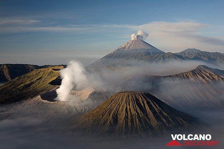 View across the Tengger caldera and an eruption at Semeru volcano. The smoking crater of Bromo volcano in the center image. (Photo: Tom Pfeiffer)