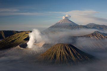 Blick im Morgengrauen über die Tengger Kaldera und ein Ausbruch am Semeru Vulkan. Der dampfende Krater des Bromo ist in der Bildmitte. (Photo: Tom Pfeiffer)