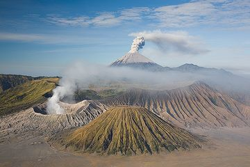 Eruption at Semeru volcano with smoking Bromo and the eroded cone of Batok volcanoes in the foreground. (Photo: Tom Pfeiffer)