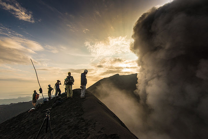 Group at the crater rim at sunrise with an eruption plume rising from the crater. (Photo: Tom Pfeiffer)