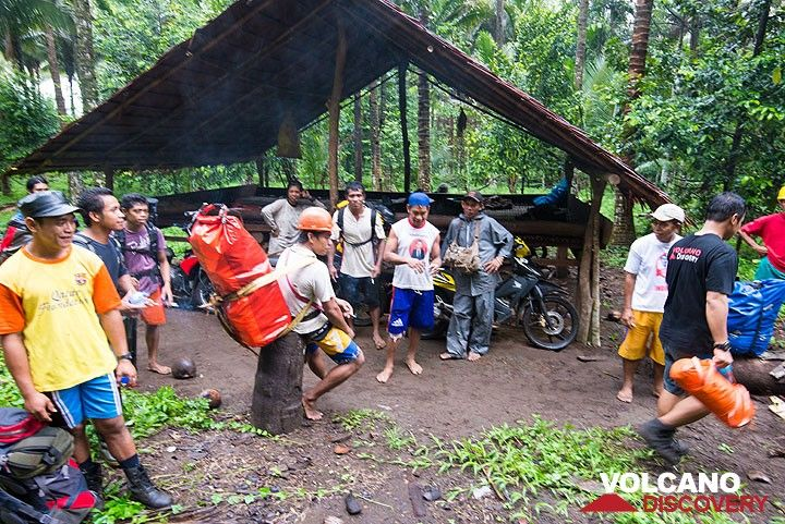 The strenuous, 5-6 hours hike up to Ibu's crater starts in a vast coconut palm plantation at the feet of the volcano. Porters gather and with the group and inspect luggage. (Photo: Tom Pfeiffer)