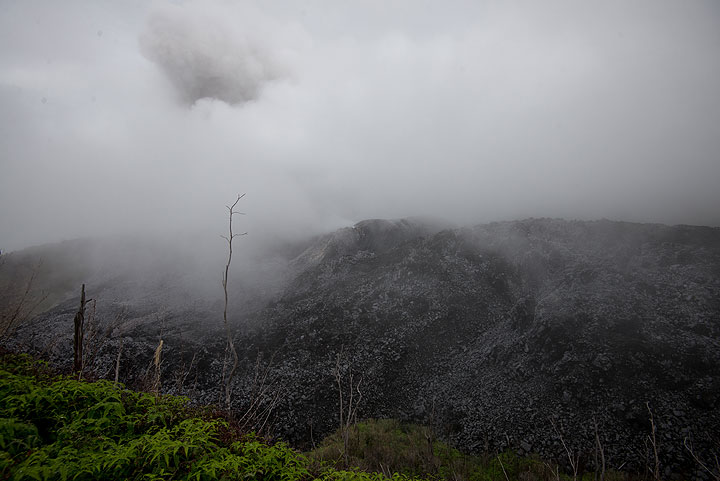 At the rim, fog obscures much of the view, but the dark menacing mass of the lava dome is visible, and an eruption plume can be guessed rising from its center. (Photo: Tom Pfeiffer)