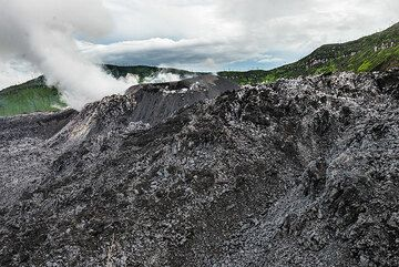 A large cinder cone has grown in the center of the lava dome of Ibu. At its eastern base, steam rises from the effusive vent. (Photo: Tom Pfeiffer)