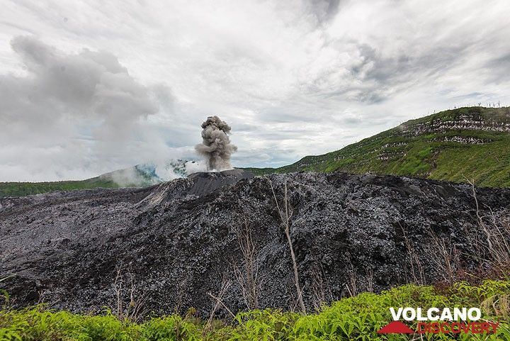 The fog lifts and gives view to the lava dome,- a viscous mass of lava that fills the crater like a giant pancake. A small eruption greets us. (Photo: Tom Pfeiffer)