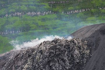 At the northeastern base of the cinder cone, another vent is active, visible as steam and hot air that blurs the background rise from there. (Photo: Tom Pfeiffer)
