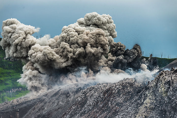 Small jets of brown and black ash, along with many small bombs are ejected during an eruption from multiple vents at the eastern base of the cone. The dark (relatively cool) finger-shaped ash jets to the right along with the white steam plumes suggest phreatomagmatic activity (i.e. interaction of water with magma). (Photo: Tom Pfeiffer)
