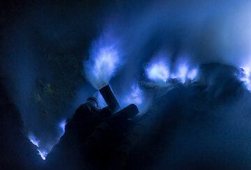 The tubes serve to collect the fumarole gasses and help condensation / sublimation of sulfur inside them. Part of the sulfur exiting as a gas burns away. (Photo: Tom Pfeiffer)