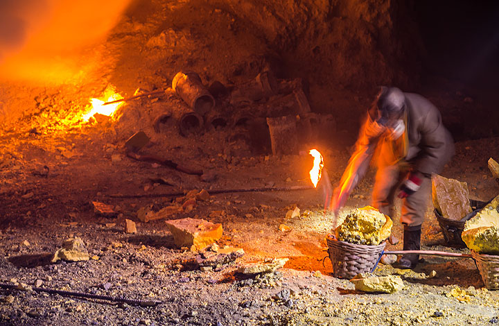A miner is filling his basket with pieces of broken solidified sulfur. (Photo: Tom Pfeiffer)