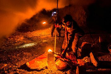 A metal bar is used to break larger pieces of sulfur crust. (Photo: Tom Pfeiffer)