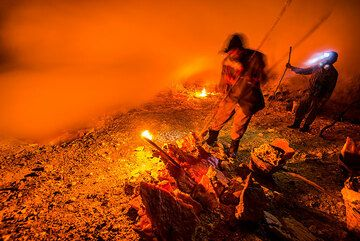 """Two sulfur workers in the mine (""""kitchen"""") at night. (Photo: Tom Pfeiffer)"""