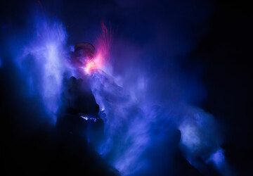 Occasionally, red sparks from liquid, burning drops of sulfur mix into the blue flames. (Photo: Tom Pfeiffer)