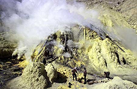 Photos of Kawah Ijen, the acid turquoise crater lake, sulfur deposits, the mining operation and workers at the site carrying baskets full of raw sulfur. (Photo: Tom Pfeiffer)