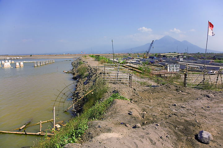 A dam is protecting an island of the original lower area to the right, where one of the last remaining factories of the area are left. Penanggungan volcano in the background. (Photo: Tom Pfeiffer)