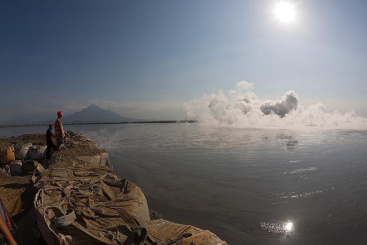 On the dam surrounding the mud vent. Penanggungan volcano in the background. (Photo: Tom Pfeiffer)