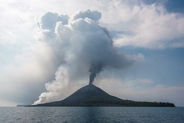 A lava flow enters the sea from Anak Krakatau on 19 Nov 2018, producing a tall steam plume. Near-continuous explosions occur at the summit vent, generating an ash plume. (Photo: Tom Pfeiffer)