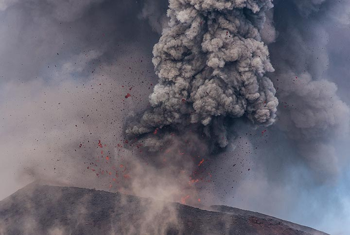 A moderately strong explosion throws many incandescent lava fragments to both sides. (Photo: Tom Pfeiffer)