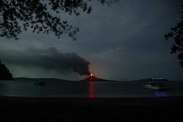 Wide-angle view of the caldera of Krakatau; our boat drifts into the picture (r). (Photo: Tom Pfeiffer)