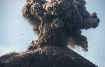 Dark bombs falling out of the ash plume. (Photo: Tom Pfeiffer)