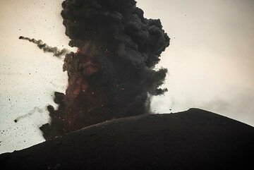 Ash-rich explosion with two large bombs leaving the eruption column on parabolic paths. (Photo: Tom Pfeiffer)