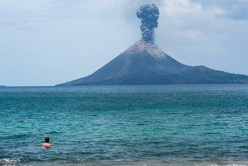 Patrick taking a swim while a vulcanian explosion occurs around noon. (Photo: Tom Pfeiffer)