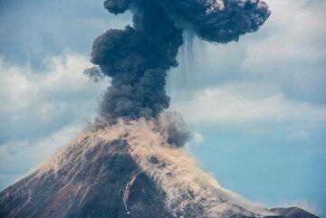 Bombs landing on the southeastern flank of Anak Krakatau, whirling up dust. (Photo: Tom Pfeiffer)