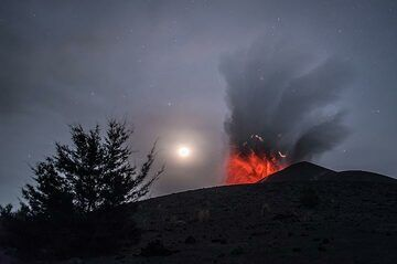 Moderate strombolian eruption with lightning in the ash plume and the setting moon (13 Oct). (Photo: Tom Pfeiffer)