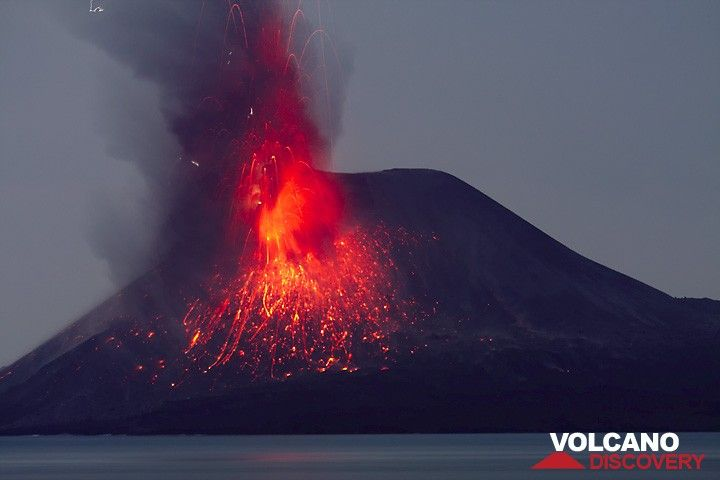 An eruption showers the s flank of the summit cone with incandescent cinders. Small lightning discharges in the eruption plume. (Photo: Tom Pfeiffer)