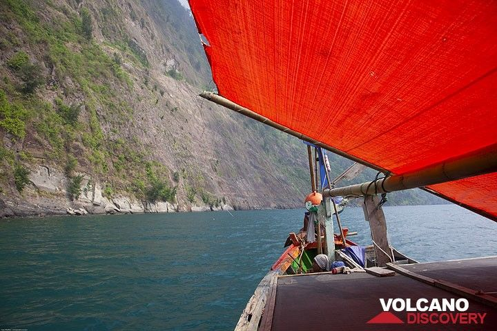 Sailing around the steep cliffs of Rakata island on a traditional fishing boat. (Photo: Tom Pfeiffer)