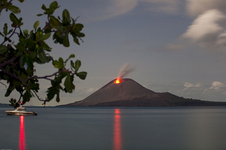 Reflections of lights of a boat and the erupting volcano on the calm sea inside the caldera. (Photo: Tom Pfeiffer)