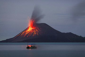 21 Nov: a small but bright eruption leaves a reflection on the calm sea.  (Photo: Tom Pfeiffer)