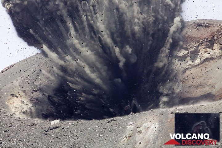 Beginning of a more powerful explosion. The plug on the conduit is thrown out and rocks separate in a fan shape spray. In the deep inside, a weak glow can be seen at some blocks. (Photo: Tom Pfeiffer)