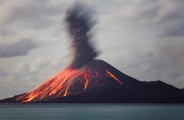 The ash plume from the previous eruption is rising while many of the incandescent blocks keep sliding down the flank. (Photo: Tom Pfeiffer)
