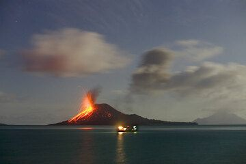 Evening of 24 Nov: a fishing boat with its too bright light moves in front of the volcano... (Photo: Tom Pfeiffer)