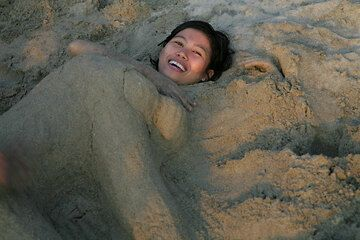 Girl buried in the sand... (Photo: Tom Pfeiffer)
