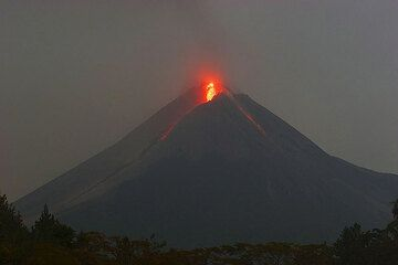 Glowing rock falls on the SW and SE sides of Merapi from the active lava dome (25 May 06). (Photo: Tom Pfeiffer)