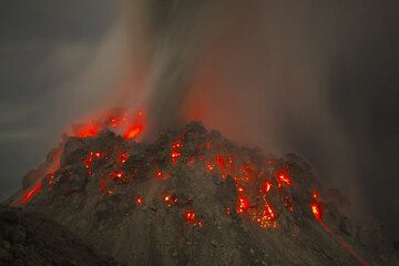 The glowing lava dome at night (30 Nov) and ash emission from a vent on the upper eastern side of the dome. (Photo: Tom Pfeiffer)