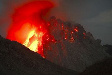 A huge block has broken off the upper eastern flank of the dome, exposing its glowing interior. (Photo: Tom Pfeiffer)