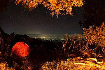 View from the basecamp at night, at 2750 m elevation near the end of the vegetation, illuminated by a campfire. A spectacular view to the NW over densely populated Java with the silhouette of Argopuro volcano (in the left). (Photo: Tom Pfeiffer)