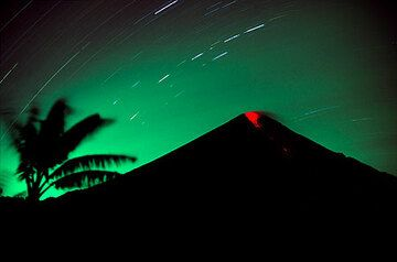 Erupting Semeru volcano at night (March 2004) - a small explosion expels incandescent bombs that roll down its southern flank. (Photo: Tom Pfeiffer)