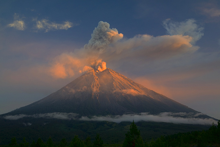 Golden morning light hits the upper slopes and parts of the ash plume from Semeru volcano. (Photo: Tom Pfeiffer)